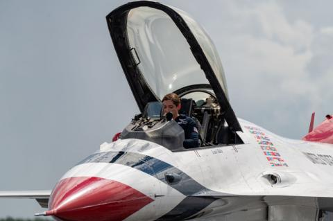 Major Michelle Curran, the lead solo pilot for the U.S. Air Force Thunderbirds gets ready to exit her F-16 after arriving in Sanford Monday afternoon.