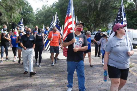 Participants walk down Park Avenue with flags and face masks during Saturday's Back the Blue march, supporting law enforcement.