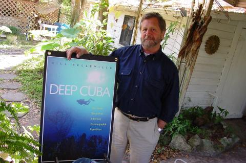 Author Bill Belleville stands in his backyard with a poster for the release of one his many books, 'Deep Cuba.'