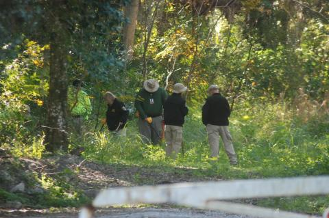 Members of the search party look for the body of Tiffany Church near E. 20th Street.