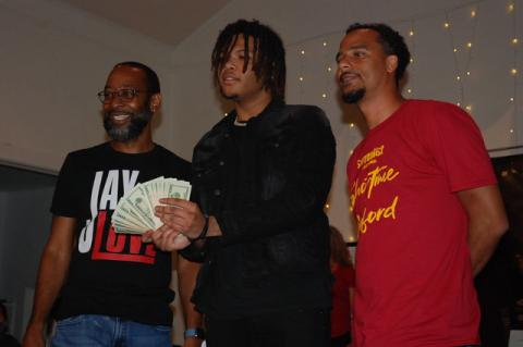 Florida Boi JJ shows off his cash prize Thursday as Showtime in Sanford host Jay Love, left, and organizer Laurence Gordon, right, look on.