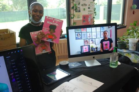 """Fair winner Lauren Jones displays her new coloring book, """"Black, Brown & Beautiful."""" She won first place recognition from the fair's judges."""