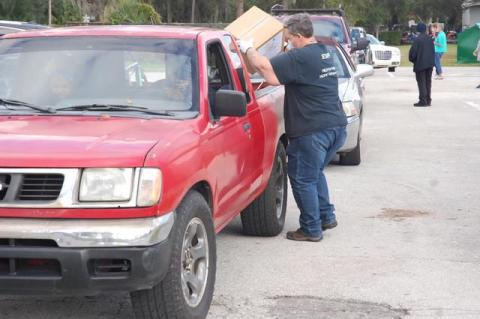 Harvest Time International staff help load vehicles with boxes of food before the holidays.