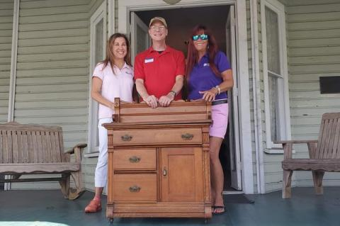 Members of the historical society show off the piece of furniture that belinged to the Bradlee-McIntyre House in Longwood.