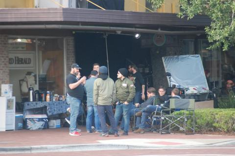 Members of a crew working in Sanford wait for the day's filming to begin on Monday at Magpies Modern General Store on 1st Street.
