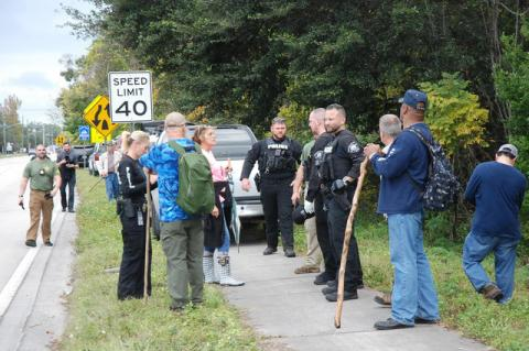 Sanford police, Seminole County Sheriff deputies and volunteers discuss the next search area after finishing a search of a wooded lot near Sanford Avenue and Airport Boulevard.