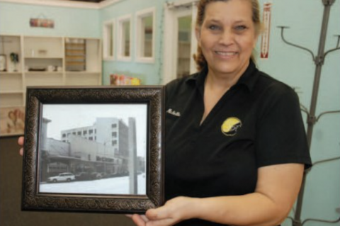 Michelle Simoneaux holds up an old photo of McCrory's store in the same location where a new country store will open.