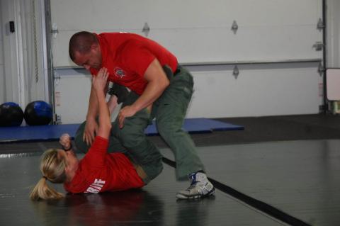 In a training exercise, Deputy Katelyn Charnas, on floor, fights off Sgt. John Martin.