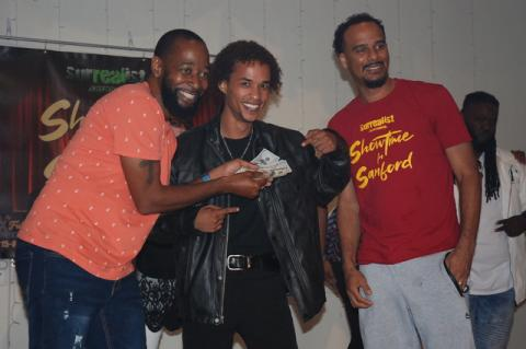 Cameron Osterloh (center), 26, of Ocala took home the $500 cash prize at October's Showtime in Sanford held Wednesday at the Woman's Club of Sanford. Cameron Osterloh poses with Showtime in Sanford host Jay love, left, and Laurence Gordon of Surrealist Entertainment, which produces the shows.