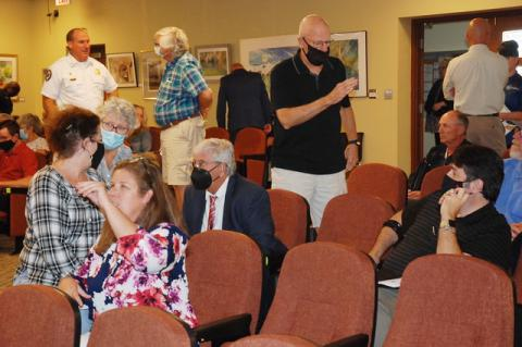 Residents from the Mayfair neighborhood talk with attorney Ralf Brookes, seated with suit and black face covering, during one of two short breaks by the Sanford City Commission during discussion on the zoning change for 3.09 acres at Mellonville Avenue and 1st Street for the proposed Vistas at Lake Monroe apartment complex.
