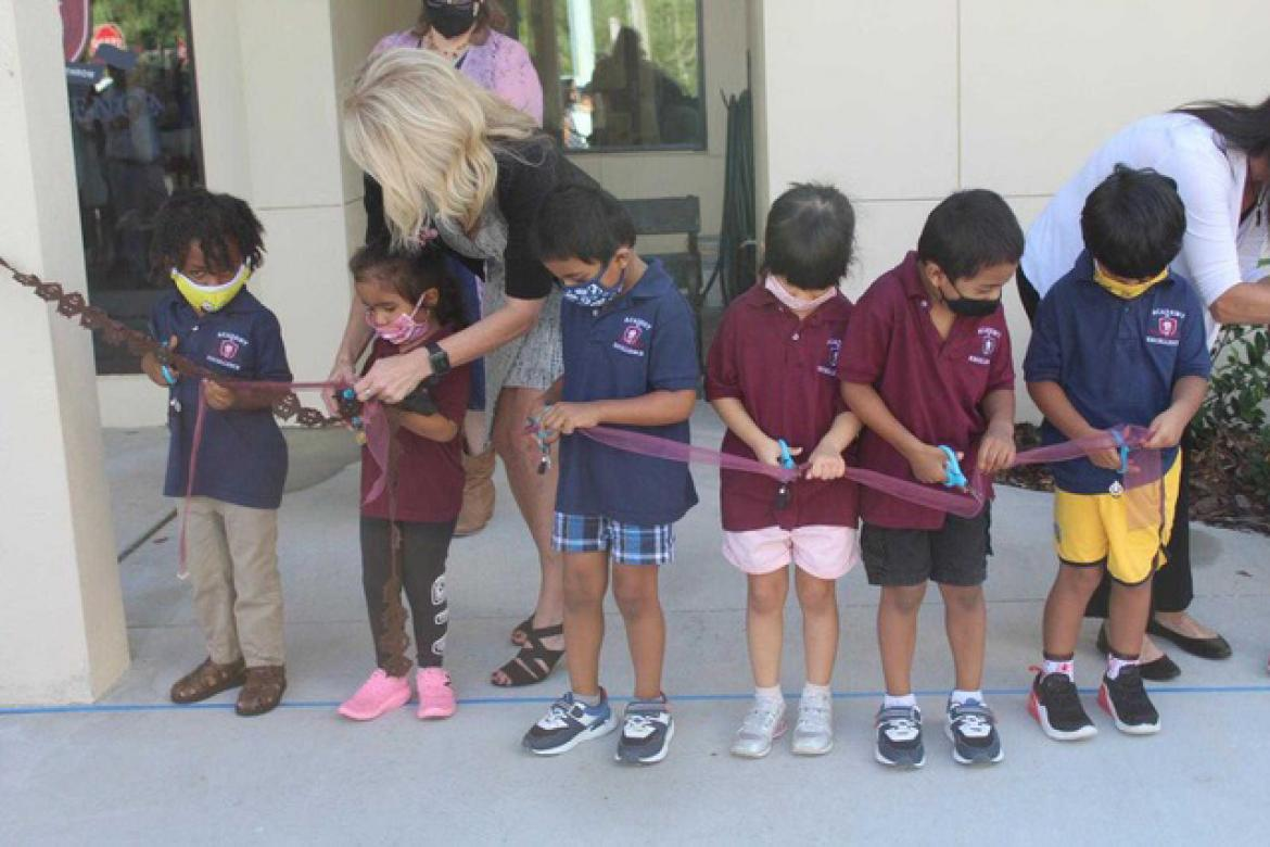 Students help cut the ribbon at the grand opening of the new campus of Academy of Excellence.