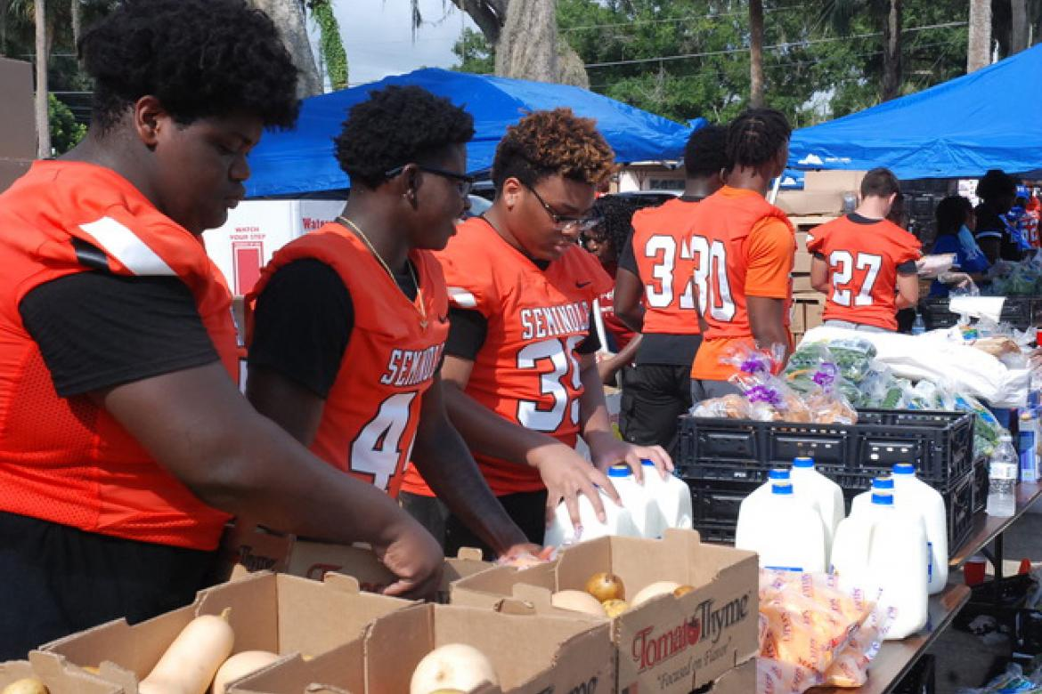 Football players from Seminole High School help with the food distribution on Friday at Allen Chapel AMEChurch.